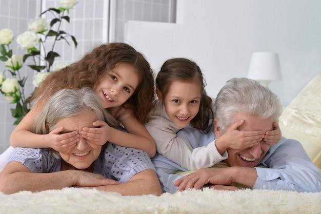 自宅で孫と幸せな年配のカップルの肖像画