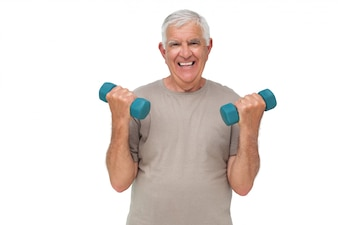 Portrait of a happy senior man exercising with dumbbells