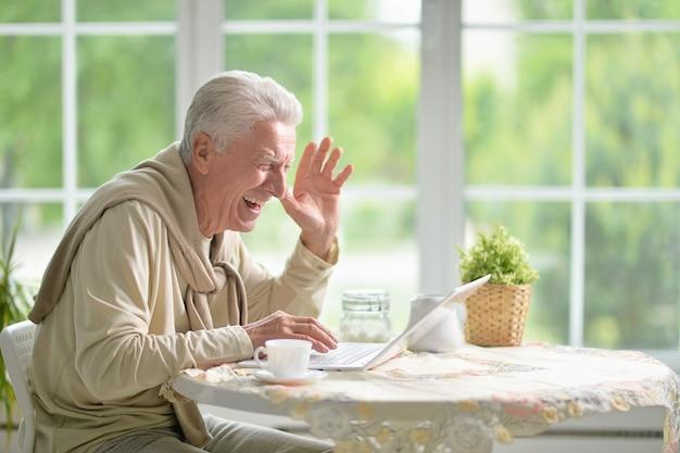 노트북을 사용하는 행복한 노인의 초상화