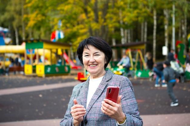 Портрет счастливой сеньоры 50 лет в парке осенью в серой куртке на детской площадке. женщина смеется и использует красный смартфон