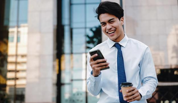 都市で携帯電話を使用して幸せな笑顔のアジア系のビジネスマンの肖像画。現代人のライフスタイル。カメラを見てください。背景としての近代的な建物