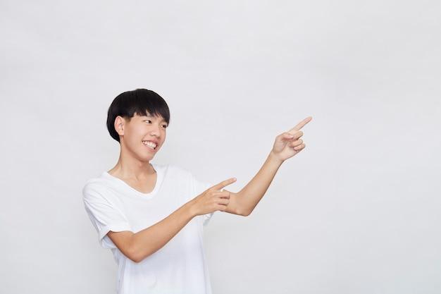 흰색 배경에 옆에 빈 공간에 손을 가리키는 캐주얼 흰색 티셔츠를 입고 행복 미소 아시아 남자의 초상화