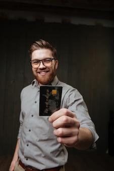 Портрет счастливого улыбающегося бородатого мужчины в очках, показывающего кредитную карту спереди, изолированную на черной деревянной поверхности