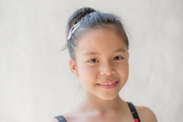 Портрет счастливой улыбающейся красивой и уверенной в себе детской девочки, смеющегося ребенка, выразительные выражения лица, место для текста, радость на лице ребенка на светлой стене, веселая и радостная концепция