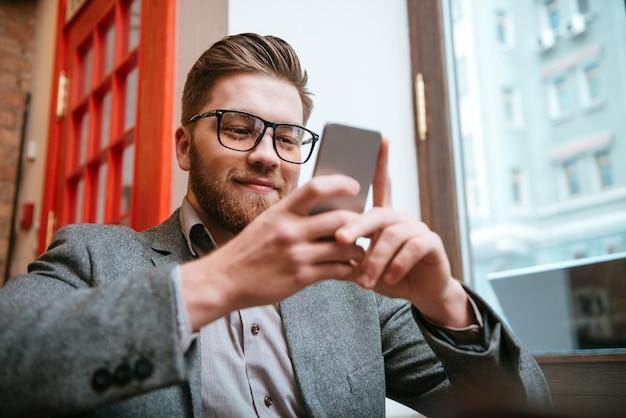 사무실에 앉아 스마트폰을 사용하여 안경을 쓰고 웃고 있는 행복한 사업가의 초상화