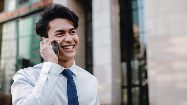 都市の携帯電話で話している幸せの笑みを浮かべてビジネスマンの肖像画。現代人のライフスタイル