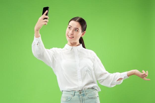緑の壁に分離された空白の画面の携帯電話を示す幸せな笑顔のカジュアルな女の子の肖像画