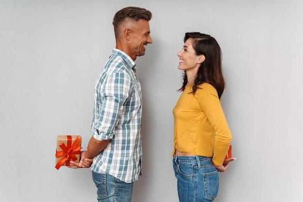 お互いに贈り物を保持している灰色の壁の上に分離された幸せな笑顔のかわいい楽観的な大人の愛情のあるカップルの肖像画