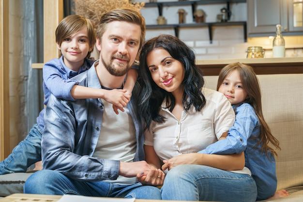 自宅で幸せな笑顔の家族の肖像画。かわいい子供男の子と女の子が両親を抱いて