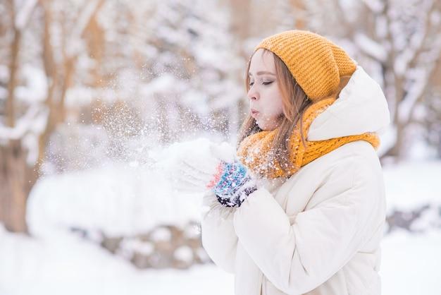 雪の降る冬の日に彼女の手から雪を吹いて幸せな笑顔の女の子の肖像画