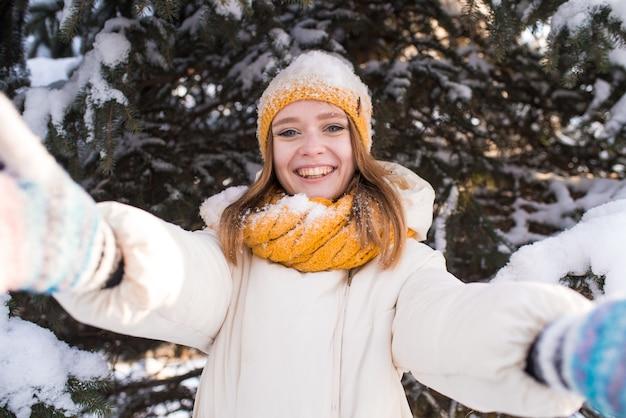 Портрет счастливой улыбающейся девушки в снежный зимний день
