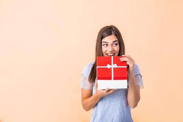 黄色で隔離のクリスマスギフトボックスを開く幸せな笑顔の女の子の肖像画