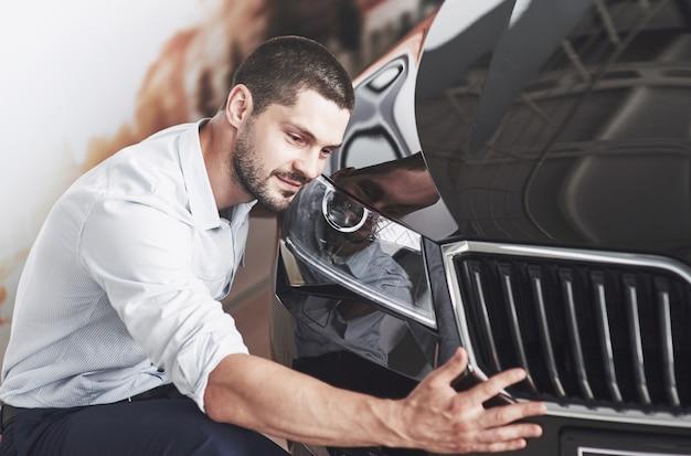 Портрет счастливого улыбающегося человека, который выбирает новую машину в салоне.