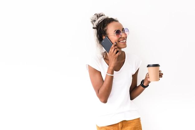 Портрет счастливой улыбающейся положительной молодой женщины с боится представлять, изолированные на белом, разговаривает по мобильному телефону, пить кофе.