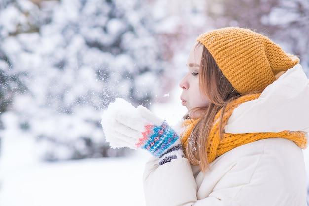 雪の降る冬の日に彼女の手から雪を吹いて幸せな笑顔の女性の肖像画