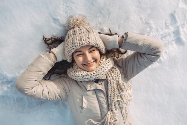 Портрет счастливой улыбающейся молодой женщины, лежащей на снегу во время солнечных зимних каникул