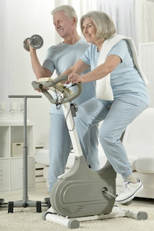 運動している幸せなスポーティな年配のカップルの肖像画