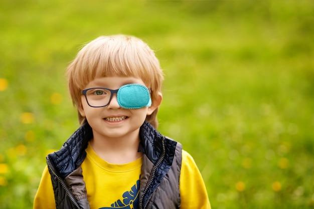 4〜5歳の幸せな斜視少年の肖像画。春の公園。