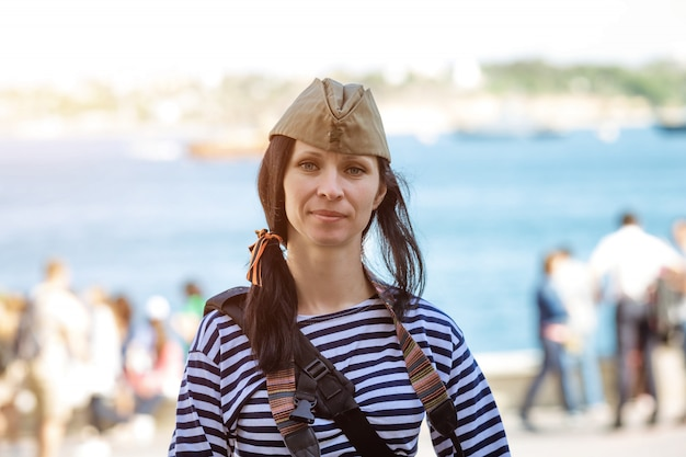 Портрет счастливой сладкой женщины в майке и военной шапочке на голове