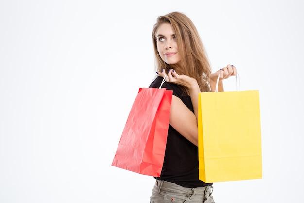 Портрет счастливой вдумчивой женщины, держащей хозяйственные сумки и смотрящей вверх, изолированной на белом фоне