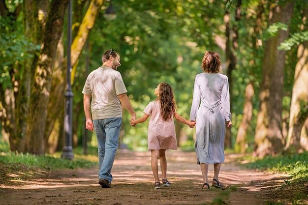 여름 공원에서 산책하는 행복한 전통 가족의 초상화, 얼굴 없는 뒤에서 보기