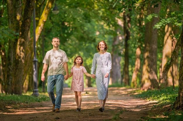 여름 공원에서 산책하는 행복한 전통 가족의 초상화