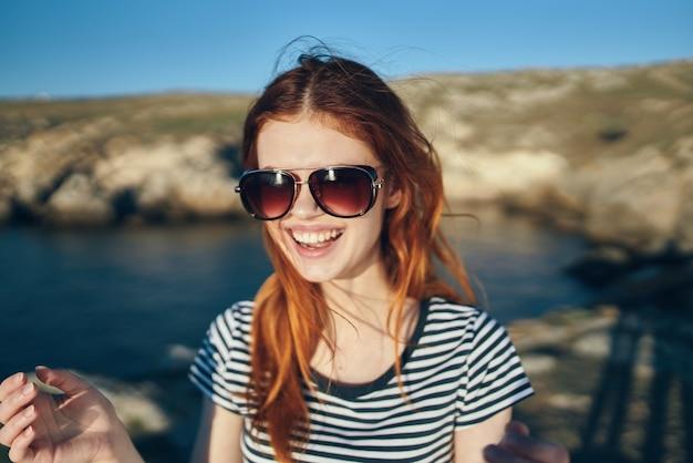 Портрет счастливого путешественника в футболке и очках у моря в горах. фото высокого качества