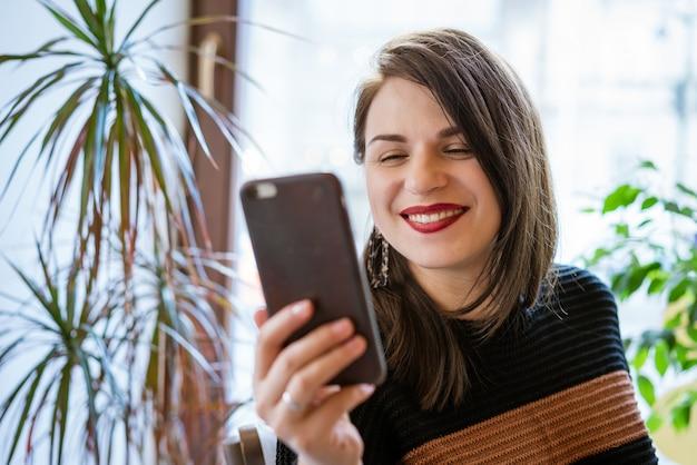 카페에서 전화 온라인 커뮤니케이션을 통해 의사 소통하는 행복한 여자의 초상화