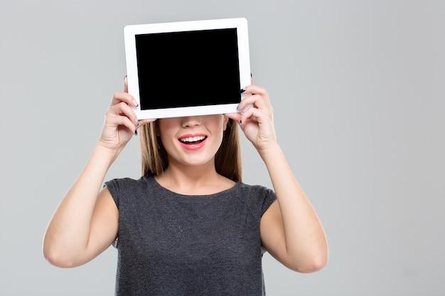 白い背景に分離された空白のタブレット コンピューター画面で彼女の目を覆っている幸せな女の肖像