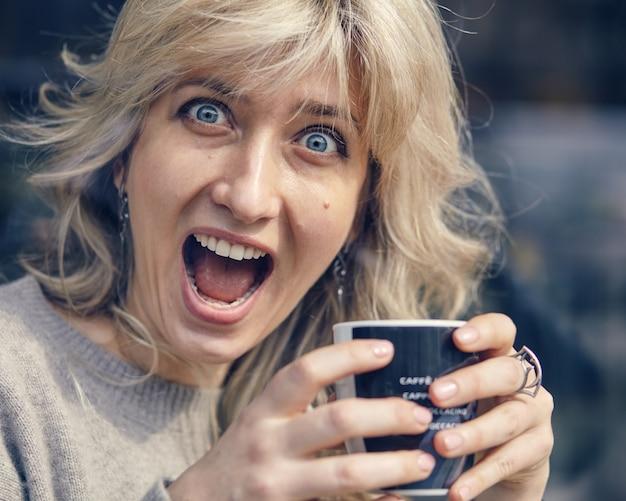 レストランでコーヒーを飲む幸せな女性の肖像画