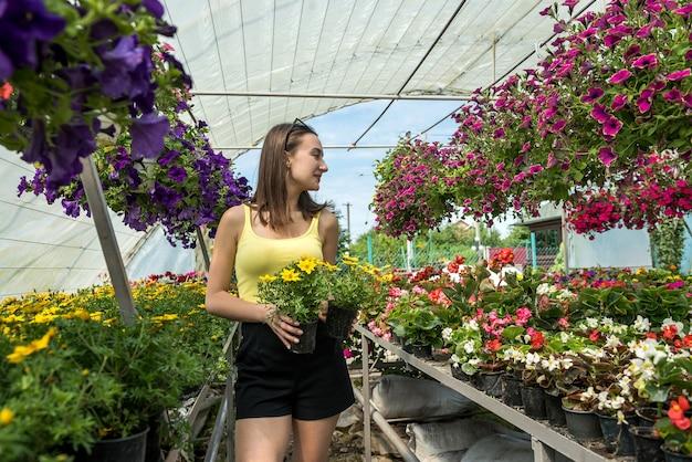 Портрет счастливой женщины-владельца парника, позирующей между ее цветами. счастливый флорист в теплице