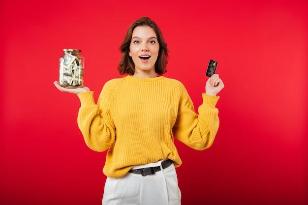 お金がいっぱい入った瓶を保持している幸せな女性の肖像画