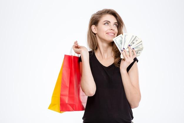 Портрет счастливой женщины, держащей хозяйственные сумки и деньги, изолированные на белом фоне