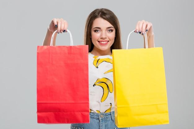 Портрет счастливой женщины, держащей хозяйственные сумки, изолированные на белом фоне