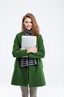 ラップトップを押しながら、白い背景で隔離のカメラを見て緑のオート麦で幸せな女の肖像