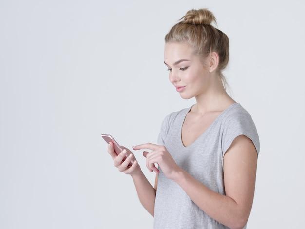 행복 한 여자의 초상화는 휴대 전화에 문자 메시지를 입력합니다-스튜디오에서