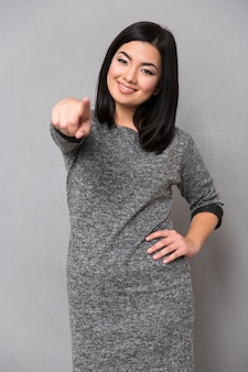 灰色の壁の前に指を指している幸せな女性の肖像画