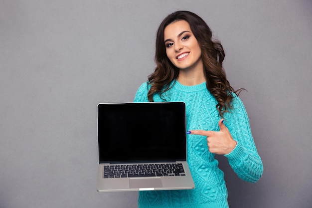 灰色の壁と空白のラップトップコンピューター画面に指を指している幸せな女性の肖像画