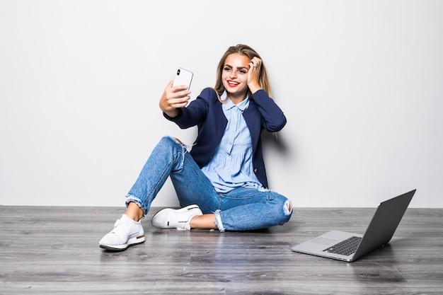 床に座って、灰色の壁にスマートフォンでselfie写真を作る幸せな女の肖像