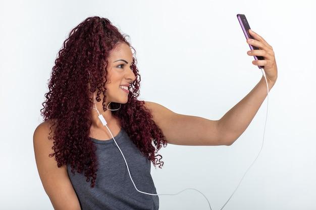 핸드폰과 이어폰을 사용하여 웃고 셀카를 만드는 행복한 여자의 초상화