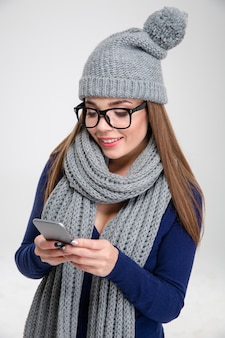 Портрет счастливой женщины с помощью смартфона, изолированной на белой стене