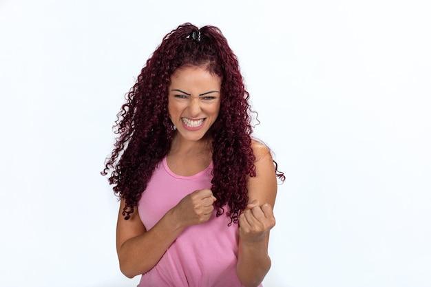 首尾よく振動し、握りこぶしを握りしめ、喜びで空気を殴る幸せな女性の肖像画。白い背景で隔離。