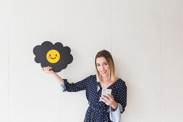 スマイルアイコンを表示している携帯電話と雲と幸せな女性の肖像