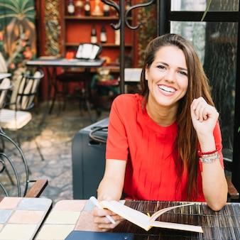 Портрет счастливая женщина с дневником, сидя в кафе