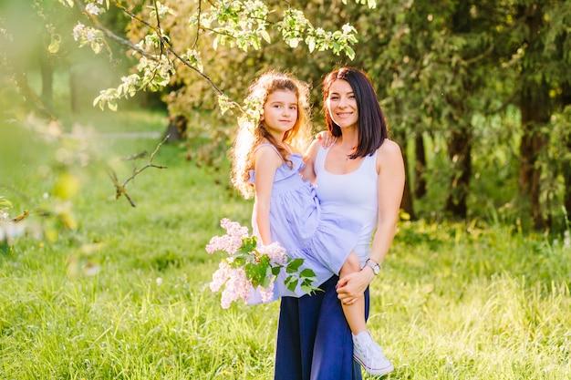 Портрет счастливая женщина с дочерью в парке