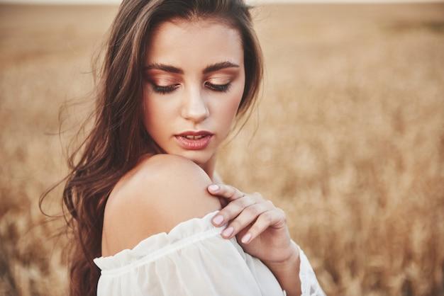 小麦畑にいる長い髪の幸せな女の肖像