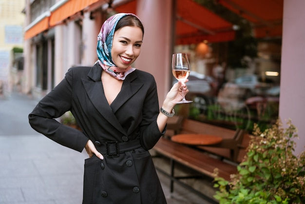 Портрет счастливой женщины с макияжем стоит возле кафе на улице с бокалом вина в руке