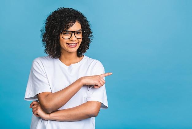 파란색 배경 위에 절연 복사 공간에서 멀리 손가락을 가리키는 행복 젊은 아프리카 계 미국인 여자의 초상화.