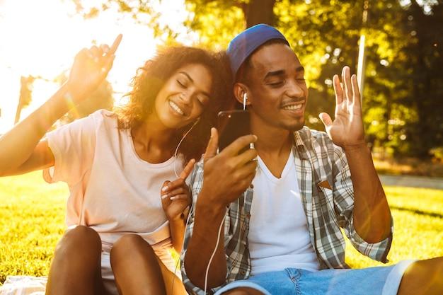 이어폰에 행복 한 젊은 아프리카 커플의 초상화