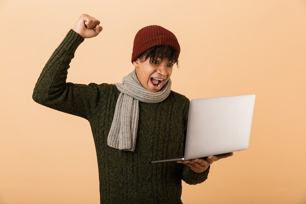 ベージュの壁に隔離された秋の服を着て、ラップトップコンピューターを保持し、成功を祝う幸せな若いアフリカ人の肖像画